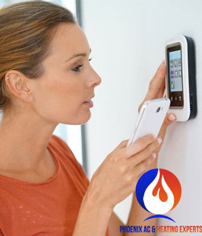 woman checking thermostat for problems